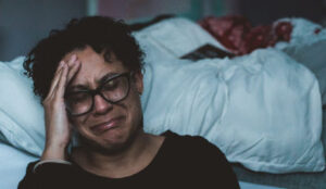 Woman sitting on the floor by her bed crying and wishing she would stop hurting.