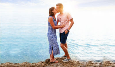 Couple on a cliff overlooking the sea kissing because they've each found the ability to trust after divorce.