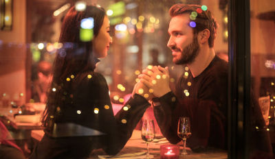Couple holding hands at a restaurant table and dating after divorce.