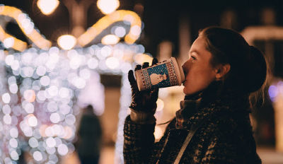 Woman drinking coffee happily looking at the lights because she's discovered how to survive divorce and the holidays.