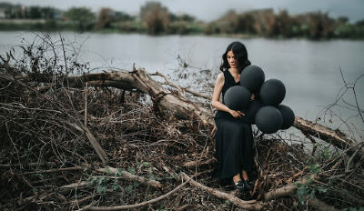Woman dressed in black holding black balloons and sitting on fallen trees.