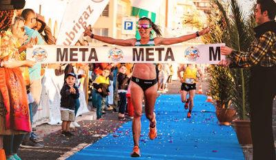 Woman running through the finish line.