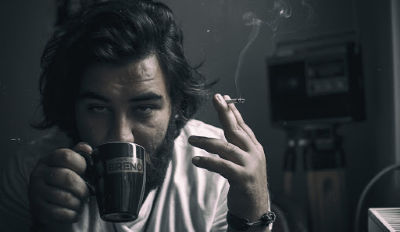Man drinking coffee, holding a cigarette and being an emotional bully.