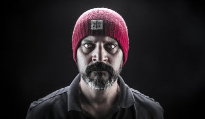 Bearded man wearing a red knit hat and staring with hatred into the camera.