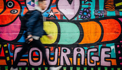 Man walking past a mural of courage as a reminder that's what healing from divorce requires.