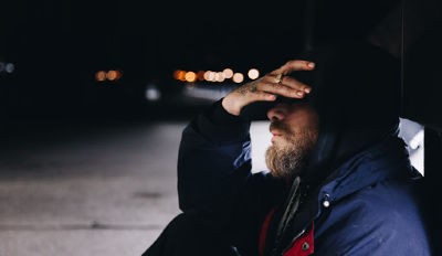 Bearded man wearing a hooded coat struggling with overcoming loneliness.