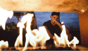 Couple sitting in front of fire as he contemplates telling her he cheated.