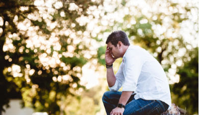Man sitting on a bench struggling with overcoming his divorce misery.