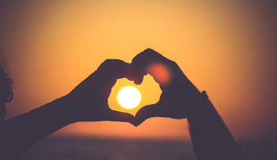 Couple making a heart over the setting sun because they've found the love of their life.