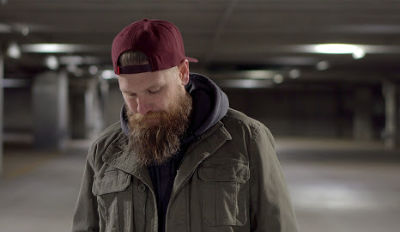 Bearded man wearing a cap and looking down as he contemplates being newly divorced.