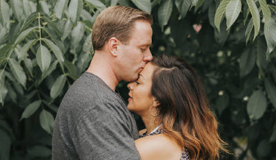 Man and woman hugging as he kisses her forehead.