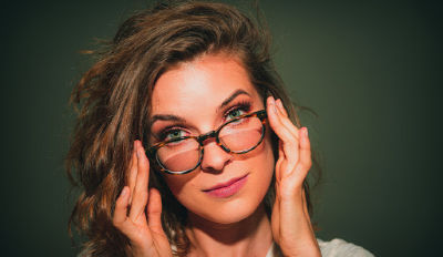 Woman confidently looking over her glasses because she's got her dignity during divorce.