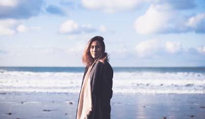 Woman walking on beach wondering how to get over a divorce.