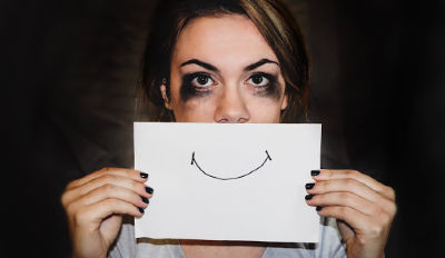 Woman who has been crying holding a drawing of a smile in front of her mouth.