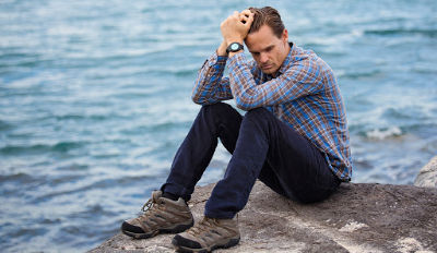 Man holding his head sitting on a boulder by the sea and wondering about the steps for divorce recovery.
