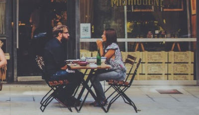Couple sitting at an outside cafe on a date.