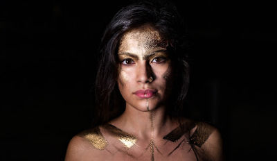 Woman in gold paint looking like a divorce superhero.