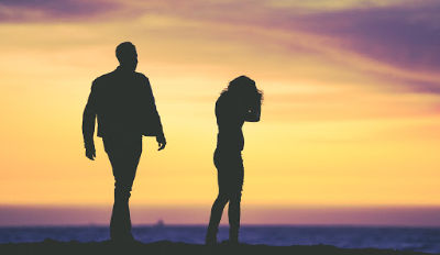Couple arguing about their unhappy marriage as they walk toward the sunset.