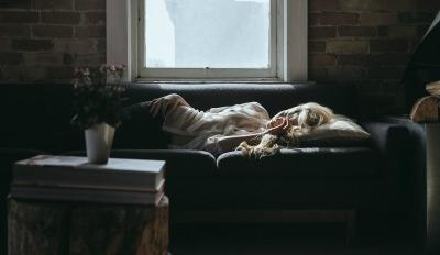 Woman languishing on the couch because she got stuck while dealing with divorce.