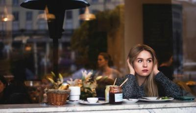 Woman in restaurant stuck in a world of negative thoughts.