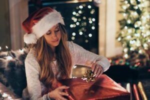 Woman contentedly wrapping a present for the holidays despite dealing with divorce.