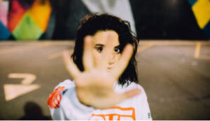Dark-haired woman holding her hand out in a stop gesture.