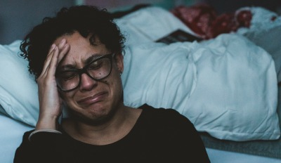 Woman sitting on the floor by her bed sobbing with grief after a divorce.