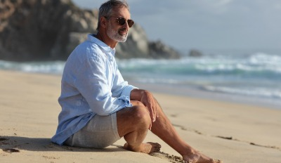 Man sitting on the beach contemplating his life after a divorce at 50.