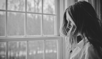 Woman by window struggling with how to overcome grief after a bitter divorce.