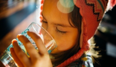 Girl drinking water unaware her parent is watching & thinking about co-parenting with a difficult ex.