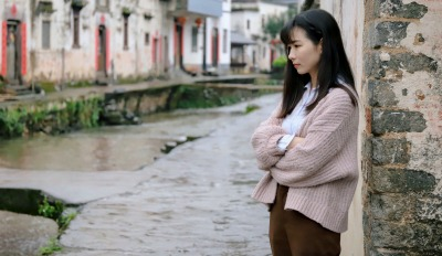 Woman standing by a canal feeling scared of life after divorce.