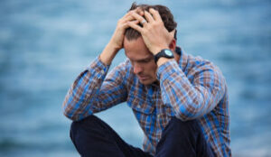 Man holding his head wondering if surviving an unhappy marriage is even possible.