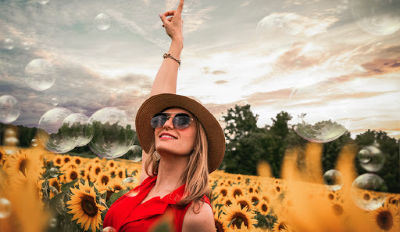 Happy woman in a field of sunflowers celebrating successfully rebuilding a life after divorce.