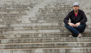 Man sitting on steps contemplating the difficulties of surviving a wife's infidelity.