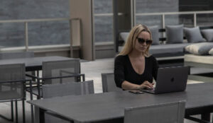Woman wearing sunglasses to hide her tears as she reads divorce quotes on her laptop.