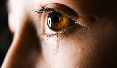 Tear falling from a woman's eye as she struggles to deal with marital infidelity.