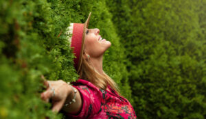 Woman leaning against a hedge enjoying the happiness in life that she's found.