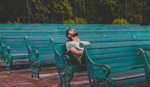 Sad man sitting on a bench struggling with ideas of how to overcome marital infidelity.