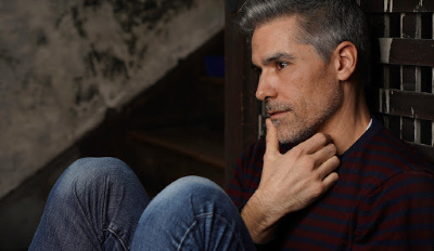 Man sitting on the floor wondering if he'll ever see signs that he's healing after divorce.