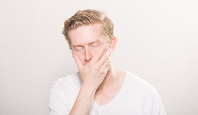 Frustrated man in white t-shirt struggling with his unrealistic expectations in marriage.