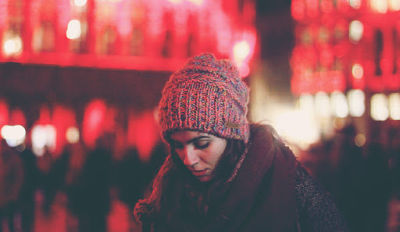 Woman wearing a red hat wondering how to begin dealing with grief after a divorce.