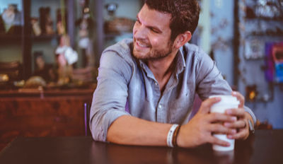 Smiling man sitting at a table enjoying his quality of life after divorce.