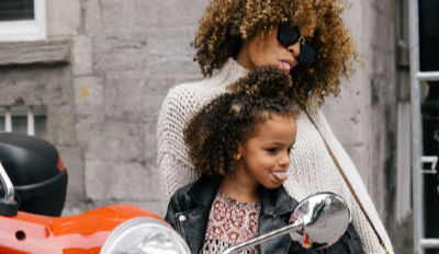 Mother and daughter sitting on a moped making faces in the mirror.