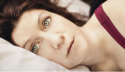 Staring woman lying with her head on a pillow struggling with healing after a divorce or breakup.