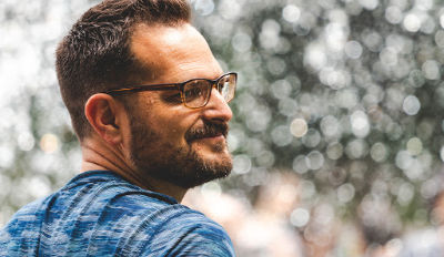 Man wearing glasses smiling because he knows his happy life will begin when you chooses it.