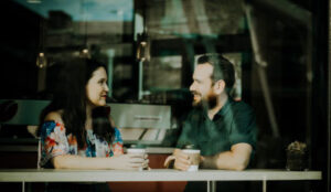 Man and woman sitting in a coffee shop exploring how self-awareness can affect communication.