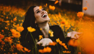 Woman sitting in a field of flowers laughing about these funny, inspirational quotes about life and happiness.