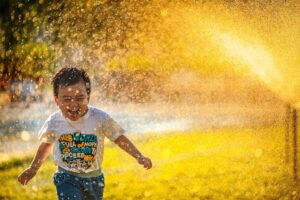 Little boy joyfully playing in a sprinkler.