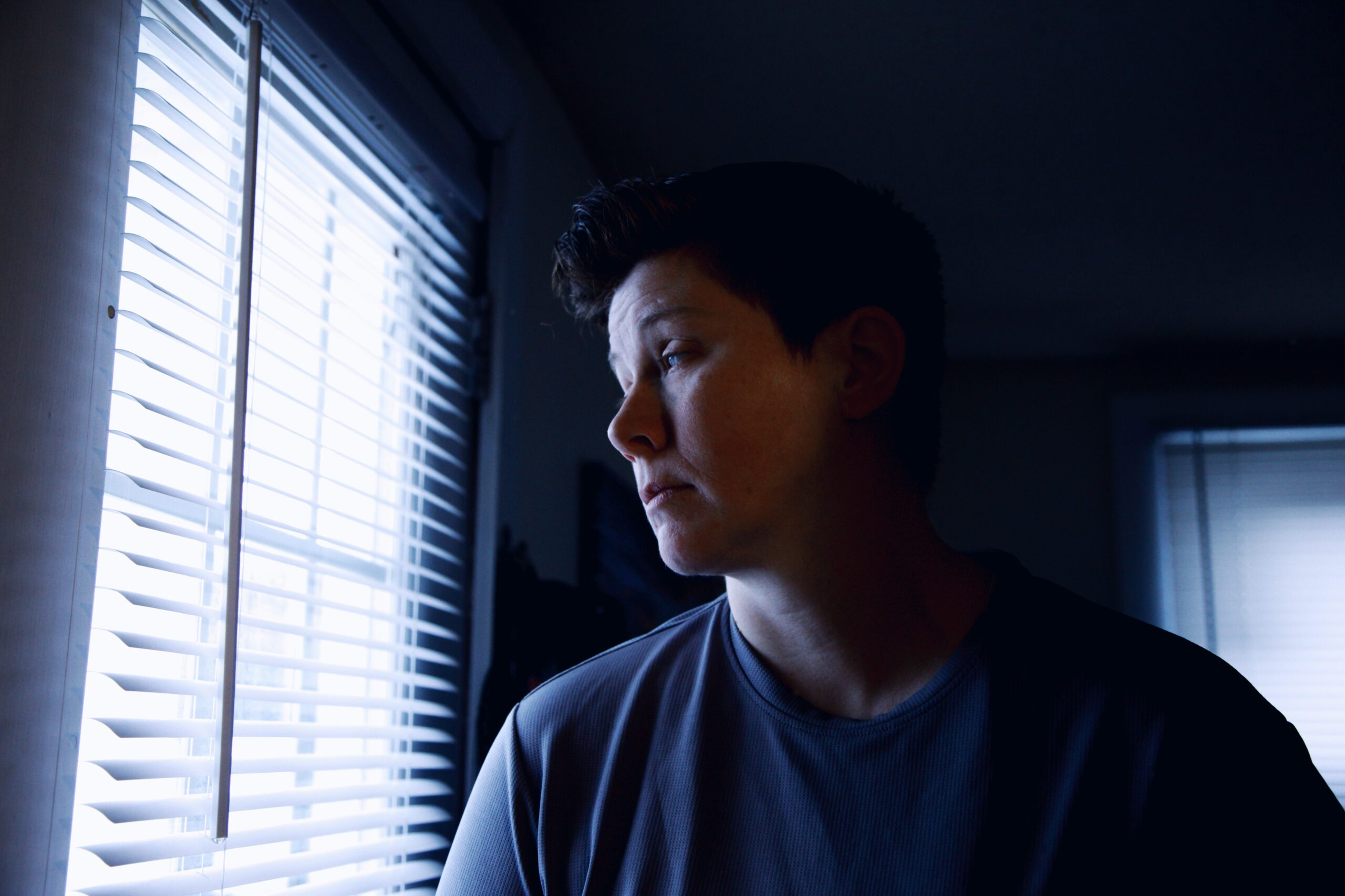 Unhappy man looking out a window wondering how he can escape his miserable marriage.