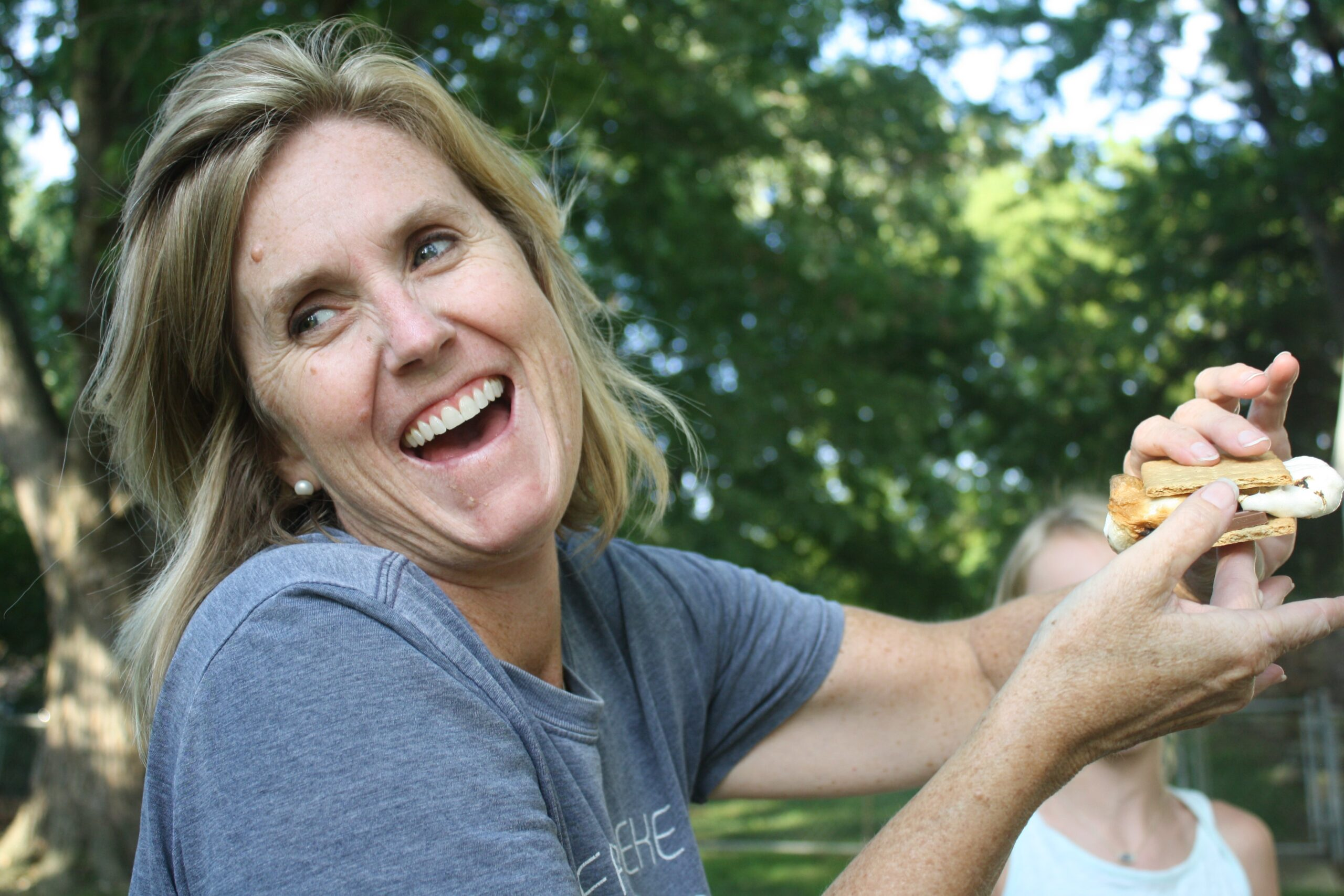 Woman laughing as she struggles with holding a s'more.